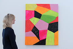 "© Licensed to London News Pictures. 07/06/2016. London, UK.   A staff member views ""Primalon Ballroom"", by the American artist Mary Heilmann, which is previewed ahead of her first major UK exhibition, ""Looking at Pictures"", at the Whitechapel Gallery.  The exhibition spans the artist's five decade career, from her early geometric paintings made in the 1970s to her recent shaped canvases in day-glo colours.  The show features approximately 45 paintings as well as a selection of ceramics, chairs and works on paper, many of which have never been exhibited.  Photo credit : Stephen Chung/LNP"