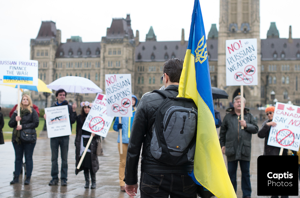 A group of Ukrainian protesters stand in front of Parliament Hill on a rainy day in Ottawa. April 26, 2014.