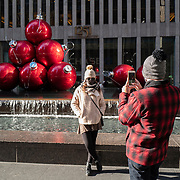 Visitors take photos in front of giant Christmas ornaments for the Holiday season during the Coronavirus (Covid-19) outbreak in Manhattan,New York on Sunday, December 6, 2020. (Alex Menendez via AP)