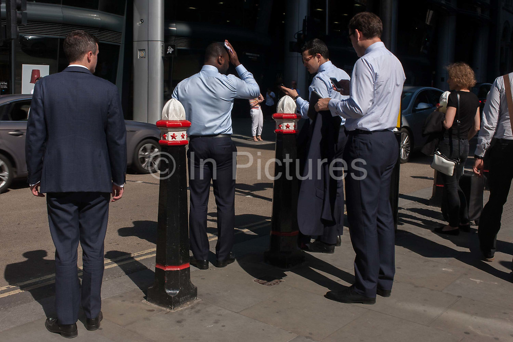 A businessman suffers from the heat and wipes his brow with a handkerchief during a heatwave on Cannon Street, on 24th August 2016, in the City of London, UK. With a few other associates, the men wait to cross the busy road running across the capitals financial district, founded by the Romans in the first Century.