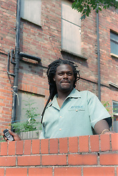 Man standing outside boarded up property holding mobile phone,