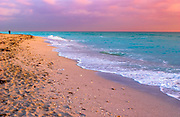 Fine Art: Early morning on a cloudy day the sunrise warms up the clousd and the beach with a man walking on the beach in the distant horizon. Turquose water and footprints in the sand are the main subjects.