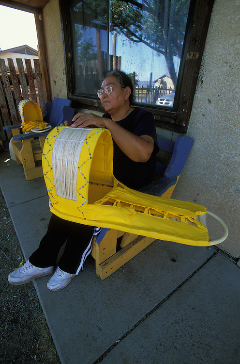 An Apache woman decorates a traditional baby cradle with beads on the San Carlos Apache Indian Reservation in Arizona, USA. June 2004.