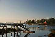 SUBJECT: Coastal Maine. IMAGE: A morning view of the Cuckold's Light off Newagen, Southport Island and the 'Witche's House' in Cape Harbor, under a seagull's supervision.