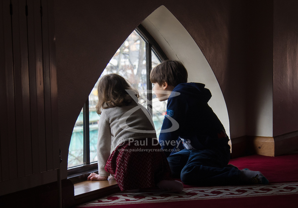 """Finsbury Park Mosque, London, February 7th 2016. Two children peer out of the upper floor window of Finsbury Park Mosque as part of a Visit My Mosque initiative by the Muslim Council of Britain to show non-Muslims """"how Muslims connect to God, connect to communities and to neighbours around them"""".<br /> . ///FOR LICENCING CONTACT: paul@pauldaveycreative.co.uk TEL:+44 (0) 7966 016 296 or +44 (0) 20 8969 6875. ©2015 Paul R Davey. All rights reserved."""