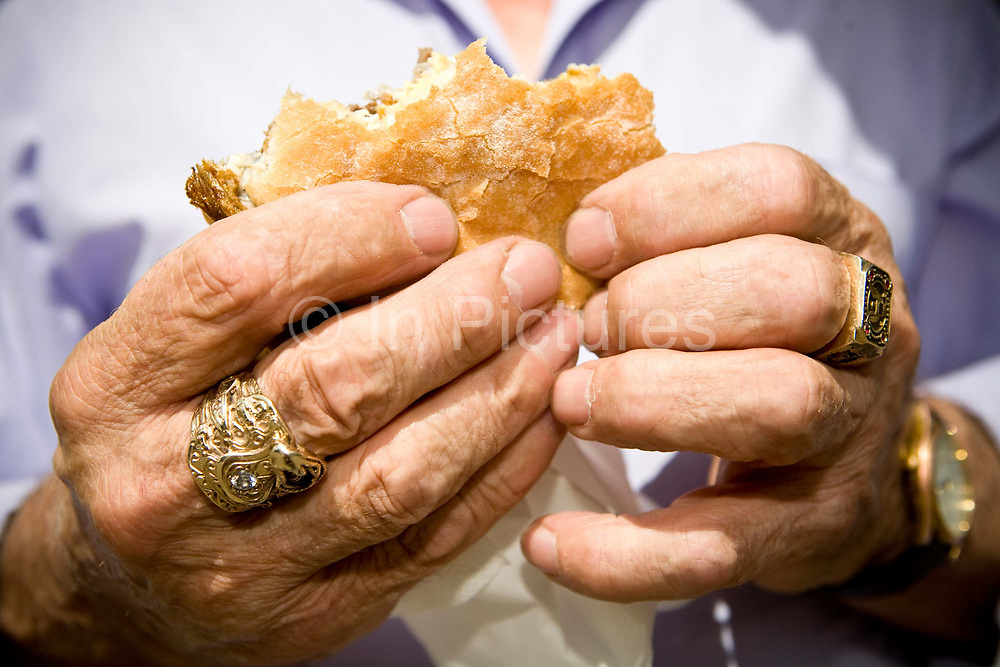An elderly man with bright gold jewellery holds a beef burger on the 25th June 2008 in Kingsley Magma in the United Kingdom.