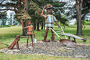 Metal child, dog, farmer, plow, and whirligig sculptures decorate a lawn on Sherman Road in Ebey's Landing National Historical Reserve, Whidbey Island, Washington, USA.