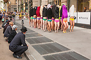 The men line the sidewalk anad watch as the women lift their dresses to revel their panties.