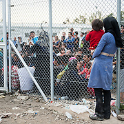 A mother with her child waits outside Moria camp, Lesvos, Greece.