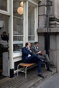 Two businessmen take coffee while checking messages outside a cafe on Threadneedle Street in the City of London, the capitals financial district, on 3rd May 2019, in London, England.