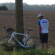 Triathlete Paul Parrish stops for a toilet break during the cycle section of his Arch to Arch triathlon attempt in northern France September 16, 2014.