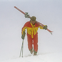 A young man carries his skis in whiteout at Mount Baker Ski Area.