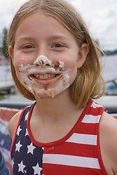 United States, Washington, Black Diamond, Girl (age 7) with pie on face, in American flag shirt.  MR