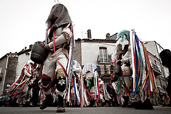 """Tricarico (MT) 06/03/2011 - Il Carnevale 2011. Il carnevale di Tricarico (Basilicata), caratterizzato dalle maschere delle mucche e dei tori che rappresentano una mandria in transumanza, è una delle manifestazioni più importanti della regione. Le """"mucche"""" e i """"tori"""" sono impersonati da uomini (la partecipazione è interdetta alle donne). I partecipanti mimano l'andatura ed i movimenti degli animali, comprese le """"prove di monta"""" dei tori sulle mucche. Tricarico e le sue maschere nel 2009 sono entrate a far parte della FECC, Federazione Europea Città del Carnevale (Federation of European Carnival Cities). La maschera da mucca è costituita da un cappello a falda larga coperto da un foulard e da un velo e riccamente decorato con lunghi nastri multicolori che scendono fino alle caviglie; la calzamaglia indossata (o, in alternativa, maglia e mutandoni di lana) è anch'essa decorata con nastri o foulards dai colori sgargianti al collo, ai fianchi, alle braccia ed alle gambe. La maschera da toro è identica nella composizione ma si distingue per essere completamente nera con alcuni nastri rossi. Ogni maschera ha un campanaccio, diverso nella forma e nel suono a seconda che si tratti di mucche o di tori."""