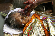 Ritual waters from the Ganges River are poured onto the face of the body of Savitridevi Mishra, who lived near the cremation grounds of Jalasi Ghat. Wrapped in a shroud of yellow and gold and decorated with marigold garlands, the woman will be burned upon a funeral pyre at the cremation grounds in a rite officiated by the eldest living male in her family.