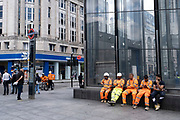 Workmen sitting in a line taking a break at a construction site along Oxford Street on 10th August 2021 in London, United Kingdom. There workers in high visibility clothing sit outside the new exterior of Tottenham Court Road underground station, which will connnect to Crossrail, or the Queen Elizabeth Line.