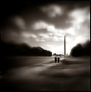 Two individuals walk down the mall at the Washington Monument. The monument is a United States Presidential Memorial constructed for George Washington and is among the world's tallest masonry structures.