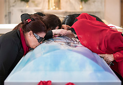 © Licensed to London News Pictures. 21/04/2018. Cobham, UK. Family members kiss the casket at the funeral of Queenie, Elizabeth Doherty from Sacred Heart Church in Cobham, Surrey. Elizabeth Doherty, whose son Paddy Doherty is known for appearing on My Big Fat Gypsy Wedding and winning Celebrity Big Brother 8, died of a heart attack earlier this month. Paddy Doherty claimed his mother has died of a 'broken heart' following the death of her husband almost a year ago. Photo credit: Peter Macdiarmid/LNP