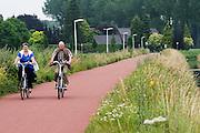 Bij Nijmegen rijden oudere fietsers op een elektrische fiets over het Rijn-Waalpad, de snelfietsroute tussen Arnhem en Nijmegen. Als de route helemaal klaar is, kunnen fietsers binnen 40 minuten van Arnhem naar Nijmegen fietsen. De snelfietsroute kent weinig obstakels en moet het aantrekkelijk maken om ook langere afstanden met de fiets af te leggen.<br /> <br /> Cyclists ride with an electrical bike on the Rijn-Waalpad, the fast cycling route between Arnhem and Nijmegen. When the route is finished, cyclists can get within 40 minutes from Arnhem to Nijmegen. The fast cycle route has few obstacles and to make it attractive to commute long distances by bicycle.