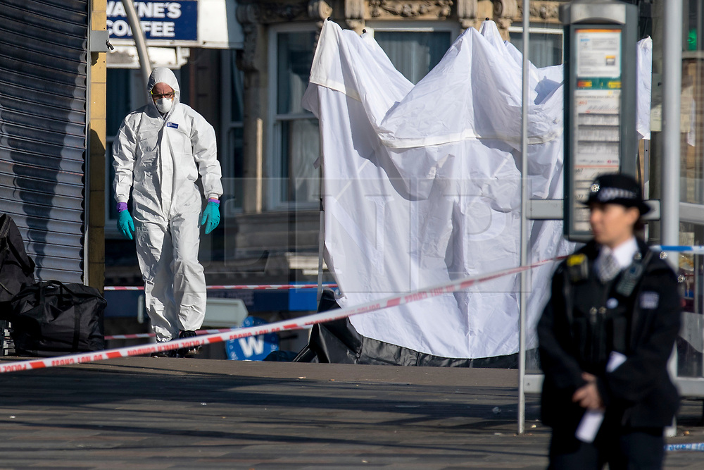 © Licensed to London News Pictures. 27/02/2019. London, UK. Forensic investigators attend the scene outside Ilford Station, where a 20-year-old man was fatally stabbed last night. A murder investigation has been launched. Photo credit: Rob Pinney/LNP