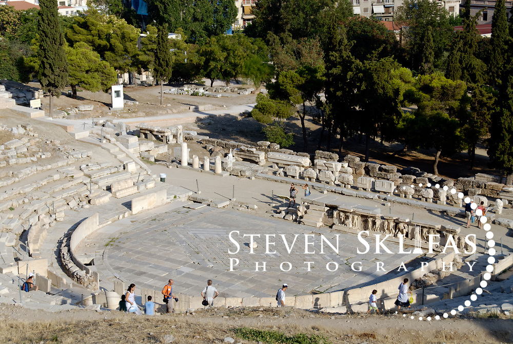 Athens. Greece.  View of the Theatre of Dionysos on the southern slope of the Acropolis in Athens. The Theatre was originally established in the 6th century BC and enlarged and improved over the Classical, Hellenistic and Roman periods and was the first theatre built of stone. The famous tragedies of Aeschylus, Sophocles and Euripides and the comedies of Aristophanes were first performed here in the 5th century BC. What is seen today is largely from the 4th century BC during the time of Lycurgus, who controlled public investment in Athens from 338 to 324 BC. The structure has 25 surviving tiers of seats from the original 65 and had a capacity to seat 17,000 spectators. The Stage front is Roman and is represented by the Bema of Phaedrus, which has 2nd century AD decorative reliefs showing scenes in the life of Dionysus, god of wine and patron god of the Greek stage.