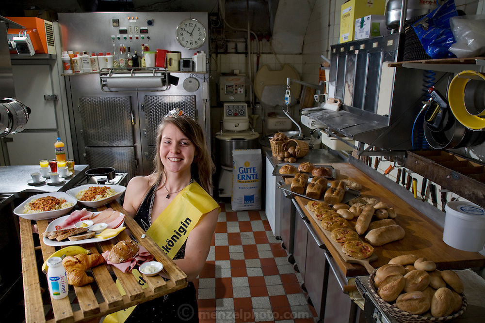 Robina Weiser-Linnartz, a master baker and confectioner with her typical day's worth of food in her parent's bakery in Cologne, Germany. (From the book What I Eat; Around the World ion 80 Diets.) The caloric value of her day's worth of food in March was 3700 kcals. She is 28 years of age; 5 feet, 6 inches tall; and 144 pounds. She's wearing her Bread Queen sash and crown, which she dons whenever she appears at festivals, trade shows, and educational events, representing the baker's guild of Germany's greater Cologne region. At the age of three, she started her career in her father's bakery, helping her parents with simple chores like sorting nuts. Her career plan is to return to this bakery, which has been in the family for four generations, in a few years. She will remodel the old premises slightly to allow customers the opportunity to watch the baking process, but plans to keep the old traditions of her forebears alive. MODEL RELEASED.