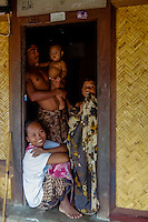 Nusa Tenggara, Lombok, Sade. Sade village. A Sasak family in a traditional Sasak house.