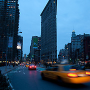 Yellow taxi passing by Madison Square and Flatiron building in New York in the evening