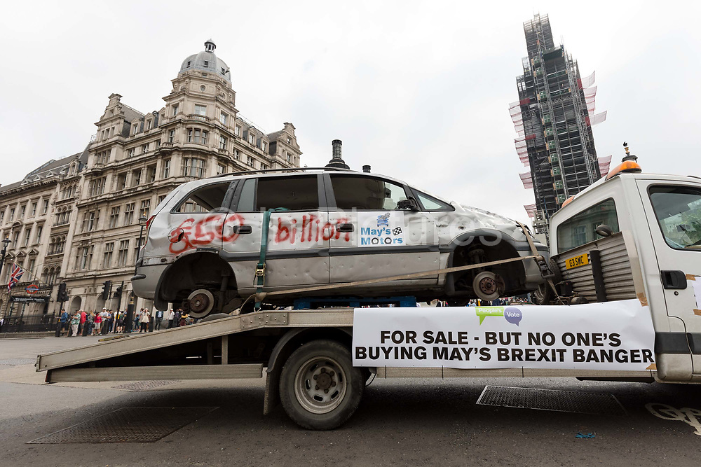 """The Brexit Banger, a bashed-up car without wheels and decorated with a banner that proclaims """"For Sale – But No One's Buying May's Brexit Banger"""" is driven around Parliament Square in London, England on July 12, 2018 on a low loader from """"May's Motors"""" on the day the Government publish their White Paper on Brexit. The People's Vote campaign claim that Prime Minister, Theresa May's Brexit proposal is set to cost taxpayers £50 billion."""