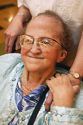 Elderly woman wheel chair user with friends hand on her shoulder at a social event organised by disability friendship club,