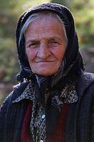 Old woman's portrait in the garden of her nearby farmhouse in the village of Isverna. Mehedinti Plateau Geopark, Geoparcul Platoul Mehedinți, Isverna, Romania.