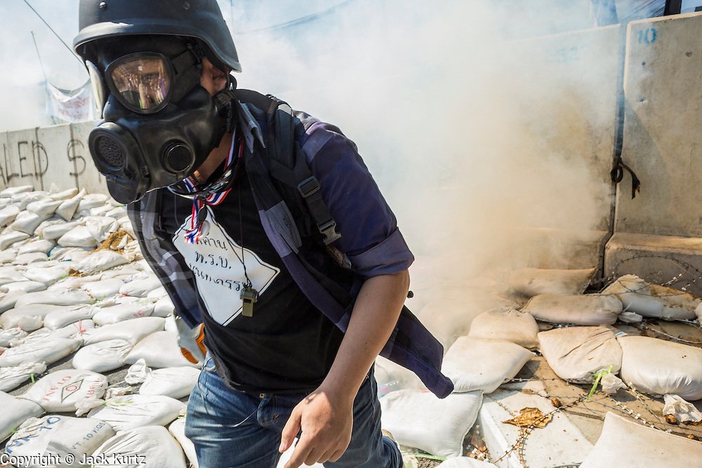 01 DECEMBER 2013 - BANGKOK, THAILAND: A Thai anti-government protestor runs through a cloud of tear gas in Bangkok. Thousands of anti-government Thais confronted riot police at Phanitchayakan Intersection, where Rama V and Phitsanoluk Roads intersect, next to Government House (the office of the Prime Minister). Protestors threw rocks, cherry bombs, small explosives and Molotov cocktails at police who responded with waves of tear gas and chemical dispersal weapons. At least four people were killed at a university in suburban Bangkok when gangs of pro-government and anti-government demonstrators clashed. This is the most serious political violence in Thailand since 2010.    PHOTO BY JACK KURTZ