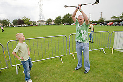 Grandfather showing grandson the skill required to use sock poi at a Parklife summer activities event,