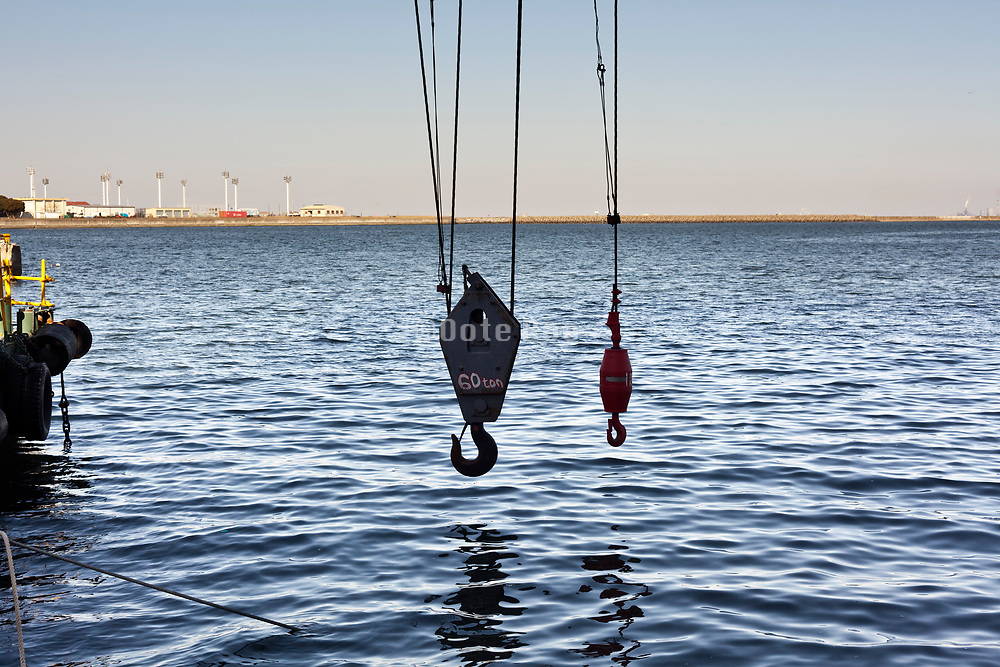 heavy 60 ton and smaller crane hook hovering above water