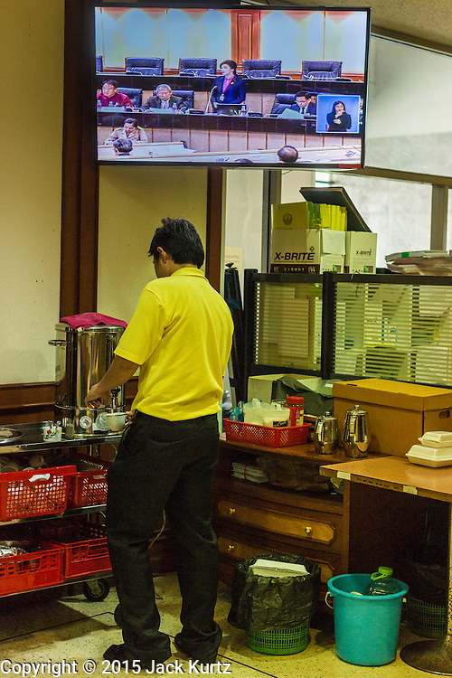 """09 JANUARY 2105 - BANGKOK, THAILAND: An employee of the National Legislative Assembly pours himself a cup of coffee while YINGLUCK SHINAWATRA is seen on a TV presenting her defense during her impeachment in the NLA. Thailand's military-appointed National Legislative Assembly began impeachment hearings Friday against former Prime Minister Yingluck Shinawatra. If she is convicted, she could be forced to stay out of politics for five years. During her defense, Yingluck questioned the necessity of her impeachment, saying, """"I was removed from office, the equivalent of being impeached, three times already, I have no position left to be impeached from."""" A decision on her impeachment is expected by the end of January.    PHOTO BY JACK KURTZ"""