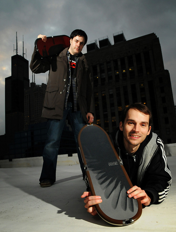 """Robomodo video game studio CEO and Creative Director David Michicich (L) and Lead Designer Patrick Dwyer show off the company's soon to be released TONY HAWK: RIDE """"skateboard"""" controller for players to stand and perform on while interacting with their on-screen persona."""