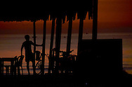 Before sunrise, early morning on a part of China beach in Danang. Silhouette of a man in a restaurant by the beach, with a table, a few chairs and bicycles. He's looking at the sea.