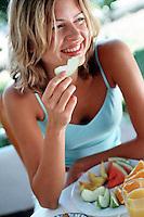 Model eating fresh fruit for magazine feature.