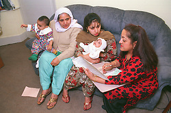 Mothers and babies talking with health visitor at baby clinic,