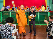 21 JANUARY 2017 - BANGKOK, THAILAND:  A Buddhist monk blesses people at a prayer service in Phra Khanong Market in Bangkok. The market serves a mix of foreign residents, local people, and Burmese migrants.      PHOTO BY JACK KURTZ