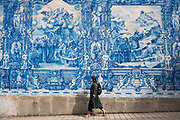 Young woman passes azulejos Portuguese blue and white wall tiles of Capela das Almas de Santa Catarina  - St Catherine's Chapel in Porto, Portugal