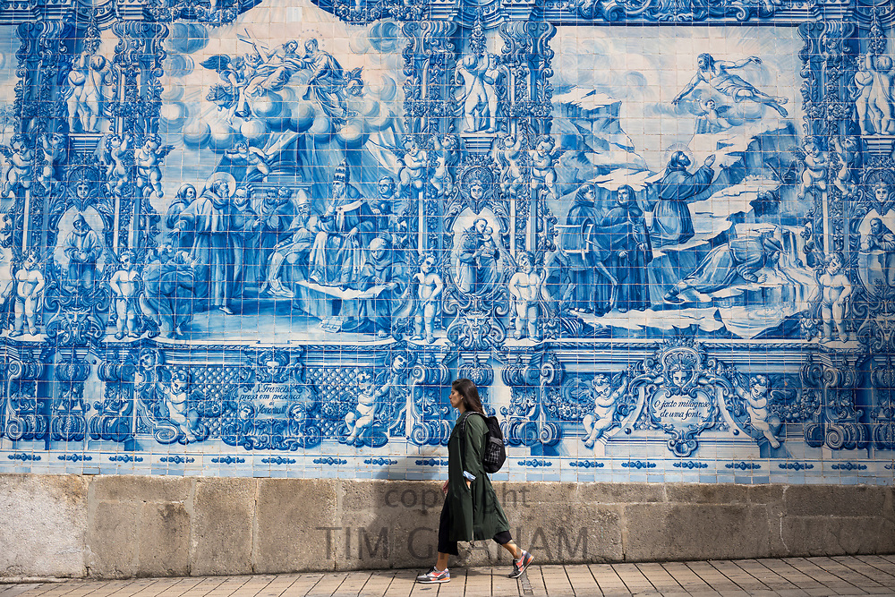 Young woman passes azulejos Portuguese blue and white wall tiles of Capela das Almas de Santa Catarina  - St Catherine's Chapel in Porto, Portugal