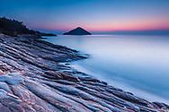 Small island with triangle form in a calm sea ad dawn