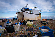 A fisherman inspects the hull of his catamaran fishing boat Julie Jean FE 380 on the beach at Dungeness in Kent on the 28th of December 2020.