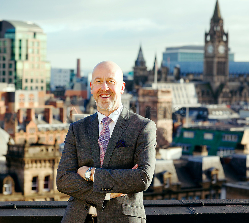 Corporate portrait taken on the roof of Black Friars house Manchester featuring head of tourism and Manchester Skyline behind