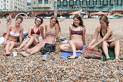 © Licensed to London News Pictures. 04/07/2014. Brighton, UK. People relaxing on Brighton Beach at lunchtime. Despite cloudy moments temperatures in parts of the south east are still expected to hit 23C. Photo credit : Hugo Michiels/LNP