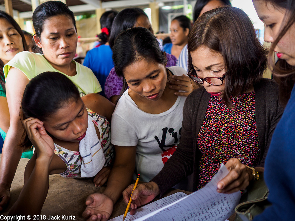 28 JANUARY 2018 - LEGAZPI, ALBAY, PHILIPPINES: Parents get coupons for free children's meals during an activity organized by Jollibee, a Filipino fast food outlet, at the evacuation shelter for people from Barangay (community) Matanag in Albay Central School in Legazpi. People from the community have been in the shelter since Mayon volcano started erupting two weeks ago. There are about 500 families at the shelter, around 2,000 people. More than 80,000 people have been evacuated from communities around the volcano and are living in shelters and camps outside of the evacuation zone. The Philippine government is preparing to house the people for up to three months.      PHOTO BY JACK KURTZ