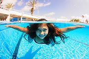 A dressed 12 year old female teen free diving under water in a swimming pool. Model release available