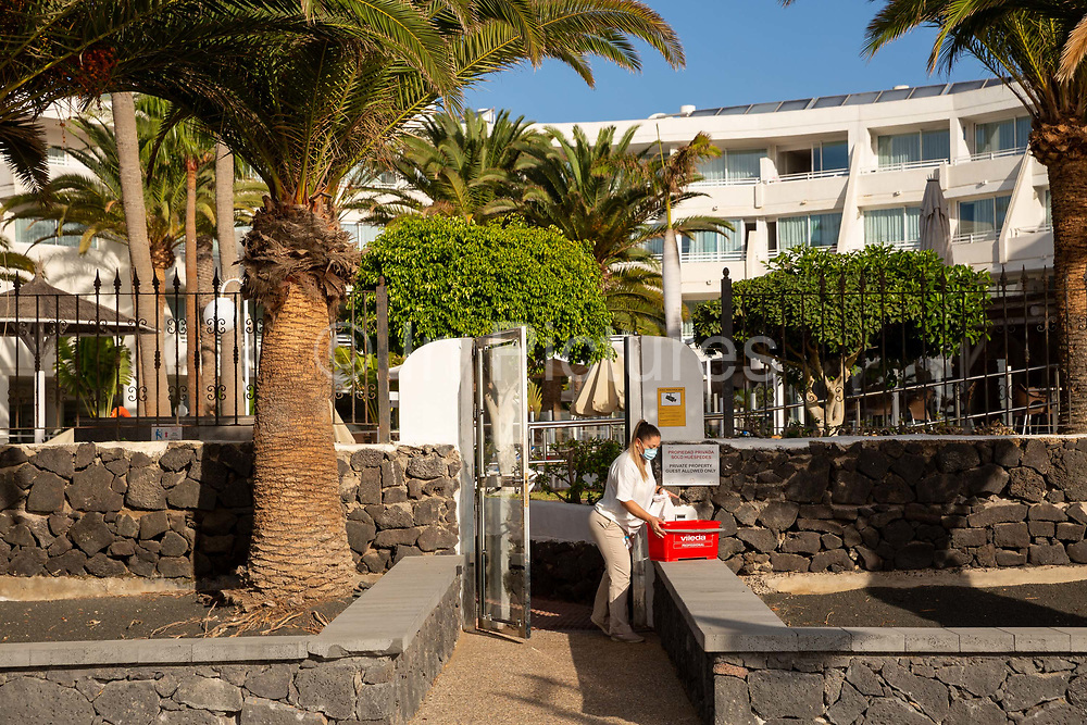 A woman in a face mask cleans and disinfects an entrance to a resort hotel in Playa Matagorda, Lanzarote, Spain on 22nd November 2020. Beaches and resorts across the island are nearly deserted since tourism plummeted due to Covid restrictions elsewhere in Europe. Although the Canary Islands have been relatively unscathed by the virus, with 155 lives lost from 2.1 million residents, the region is heavily dependent on tourism and locals are hoping that numbers recover as lockdown measures ease and vaccines potentially reduce the numbers of infections.