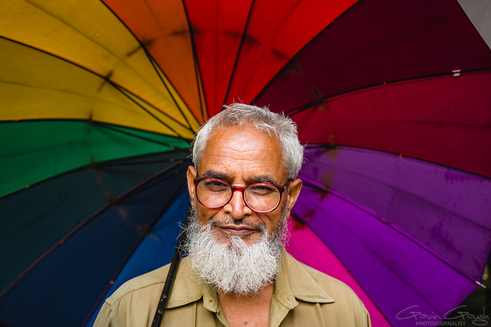 Portrait of a man with a white beard and spectacles holding a colourful, rainbow umbrella, Chhatrapati Shivaji Terminus (CST), Mumbai, India